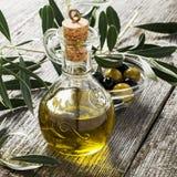 Tillbringare med extra jungfrulig olivolja på den olivgröna skärbrädan som omges av filialer av olivträdet och oliven selektivt arkivbild