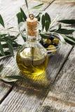Tillbringare med extra jungfrulig olivolja på den olivgröna skärbrädan som omges av filialer av olivträdet och oliven selektivt arkivbilder
