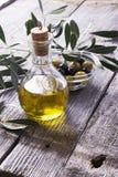 Tillbringare med extra jungfrulig olivolja på skärbrädan som omges av filialer royaltyfri bild