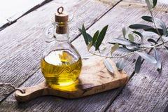 Tillbringare med extra jungfrulig olivolja på skärbrädan som omges av filialer Royaltyfri Fotografi