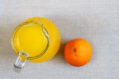 Tillbringare och exponeringsglas av orange fruktsaft och mogna apelsiner från över, bästa v Royaltyfri Foto