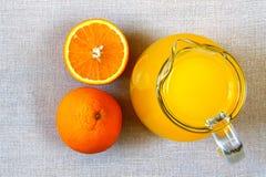 Tillbringare och exponeringsglas av orange fruktsaft och mogna apelsiner från över, bästa v Arkivfoton