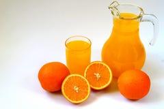 Tillbringare och exponeringsglas av orange fruktsaft och mogna apelsiner på vit Arkivfoto