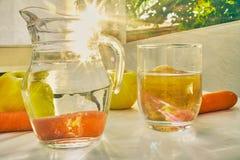 Tillbringare och exponeringsglas av vatten med frukter bakifrån royaltyfri foto