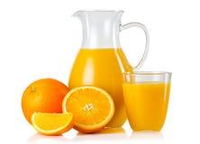Tillbringare och exponeringsglas med orange fruktsaft och frukter med isolerade skivor Royaltyfri Foto