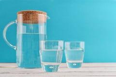 Tillbringare och två exponeringsglas med klart vatten arkivbild