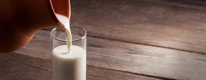 Tillbringaren av mjölkar med en tabell för gammalt land, en vit drink är hällt I royaltyfria foton