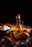 Tillbringaren med olja, baglar, ägg, kuper ett mjöl Arkivfoto
