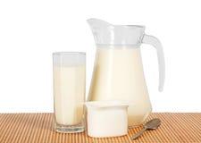 Tillbringaren och exponeringsglas med mjölkar, yoghurten Arkivfoton
