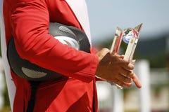 Tilldela den vinnande ryttaren i det röda omslaget som rymmer trofén Arkivfoto