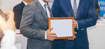 Tilldelar ett diplom av en annan man på ett affärsmöte Royaltyfria Bilder