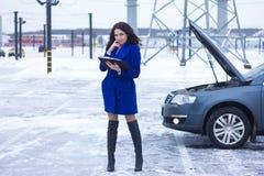 Tilldrar uppmärksamheten av en kvinna som läser en manuell bil Arkivbild