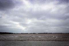 Tilled farm fields in winter with light snow and stormy clouds in Illinois royalty free stock photography