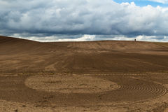 Tilled Field. Tilled / ploughed hilly earth field with cloudy blue sky in background Stock Images