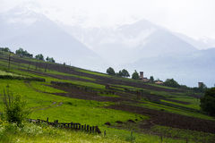 Tilled land in mountains of Georgia. Raining on tilled land with snowy mountains veiled in haze in the background. Mestia, Svaneti, Georgia. There can be seen Stock Photos