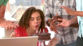 Tillfällig affärskvinna som blåser hennes födelsedagkaka arkivfilmer