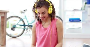 Tillfällig affärskvinna som lyssnar till musik stock video
