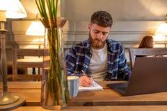 Tillfällig affärsman eller freelancer som planerar hans arbete på anteckningsboken som arbetar på bärbar datordatoren med den sma Royaltyfria Foton
