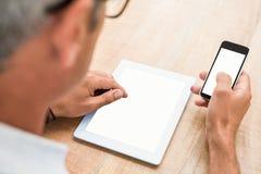 Tillfällig affärsman som använder smartphonen och minnestavlan royaltyfria foton