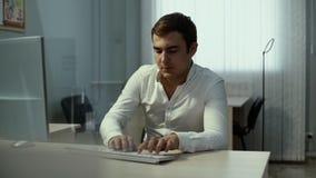 Tillfällig affärsman som arbetar i ljust kontor och att sitta på skrivbordet som skriver på tangentbordet arkivfilmer