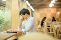 Tillfällig affärsman som arbetar med bärbara datorn i kafé Arkivfoto