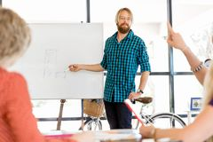 Tillfällig affärsman som ger en presentation i kontoret arkivfoton