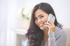 Tillfällig asiatisk kvinna som gör en påringning den hemmastadda användande smarta telefonen royaltyfri fotografi