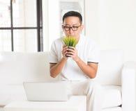 Tillfällig asiatisk man som sniffar gräs Royaltyfri Bild