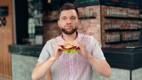 Tillfällig attraktiv man som biter den önskade läckra hamburgaren med den köttgrönsallat och grönsaken stock video