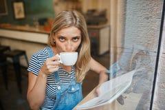Tillfällig closeupstående av kvinnan som dricker kaffe och läs- mag royaltyfria foton