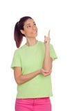 Tillfällig flicka med rosa jeans som indikerar något med fingret Arkivfoton