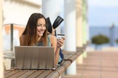 Tillfällig flicka som direktanslutet utomhus köper med en kreditkort Royaltyfria Bilder