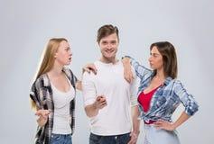 Tillfällig folkgrupp, leende stiliga Guy Beautiful Girls Point Finger för kvinna för ung man två lyckligt till dig som talar royaltyfri fotografi