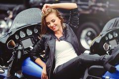 Tillfällig härlig kvinna på en motorcykel i det ljusa leendet för gata på en solig dag Royaltyfria Foton