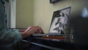Tillfällig klädd ung man som hemma använder bärbar datordanandeanmärkningar i notepad arkivfilmer