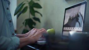 Tillfällig klädd ung man som hemma använder bärbar datordanandeanmärkningar i notepad stock video