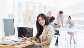 Tillfällig kvinna på skrivbordet med kollegor bakom i regeringsställning Royaltyfria Bilder