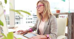 Tillfällig kvinna som i regeringsställning använder datoren lager videofilmer