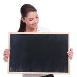 Tillfällig kvinna som ser svart tavla Royaltyfri Fotografi
