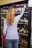 Tillfällig kvinna som tar flaskan av vin royaltyfria bilder