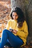 Tillfällig kvinnamessaging på den smarta telefonen i höst arkivbild