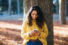 Tillfällig kvinnamessaging på smartphonen i höst royaltyfria bilder