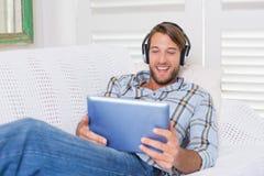 Tillfällig le man som ligger på soffan som lyssnar till musik på minnestavlaPC royaltyfri fotografi