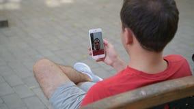 Tillfällig lycklig man som använder sammanträde för meddelande för smartphoneinspelning ett videopn på en bänk i en parkera stock video