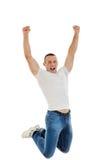 Tillfällig lycklig ung Caucasian man som griper hårt om hans nävar och hoppa royaltyfri fotografi