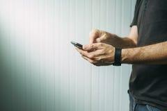 Tillfällig man som använder den smarta telefonen för att överföra textmeddelandet arkivfoton