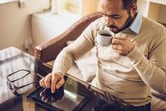 Tillfällig man som använder minnestavladatorsammanträde i kafét som surfar internet Royaltyfria Bilder