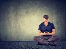 Tillfällig man som använder smartphonen, medan sitta arkivbilder