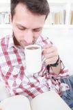 Tillfällig man som dricker kaffe eller te och läsebok arkivbilder