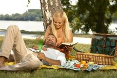 Tillfällig man som sover på picknicken i varv av flickvännen Royaltyfri Foto